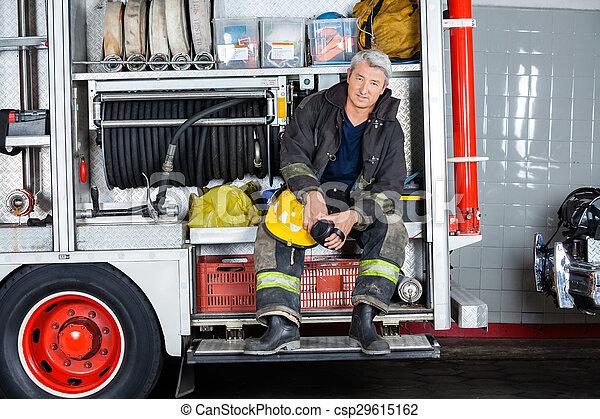 Bombero confiado sentado en un camión en la estación de bomberos - csp29615162