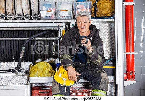 Bombero sonriente sentado en un camión en la estación de bomberos - csp29869433