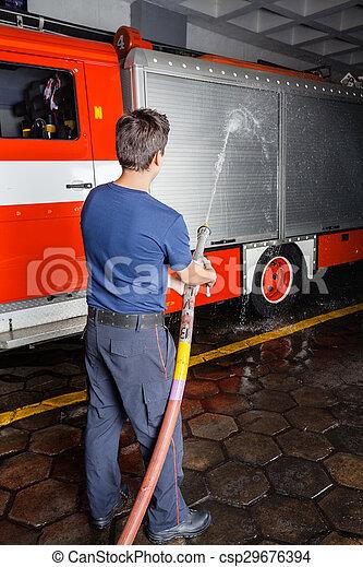 Bombero rociando agua en el camión durante la práctica - csp29676394