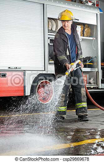 Bombero rociando agua en el suelo durante la práctica - csp29869678