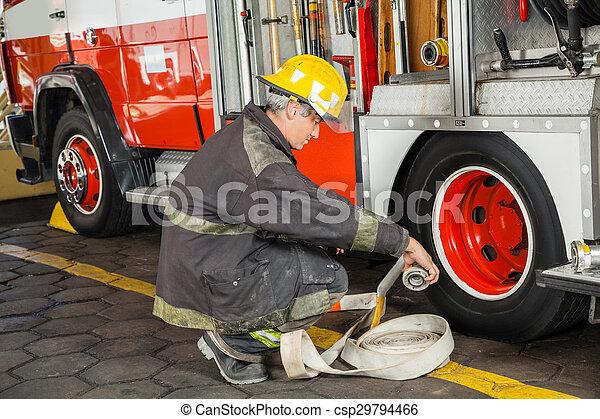 Bombero agachándose mientras sostenía la manguera en un camión - csp29794466