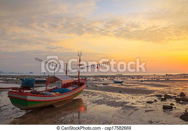Un pequeño bote de madera con bombillas para pescar calamares nocturnos en la orilla durante la marea de Ebb, Tailandia - csp17582669
