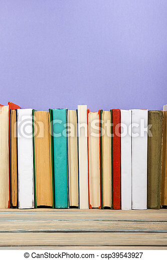 Books on grunge wooden table desk shelf in library. Back to school background with copy space for your ad text. Old hardback   no labels, blank spine - csp39543927