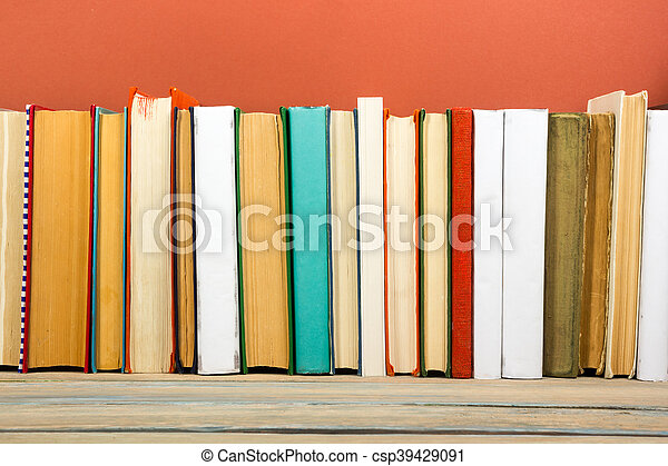 Books on grunge wooden table desk shelf in library. Back to school background with copy space for your ad text. Old hardback   no labels, blank spine - csp39429091