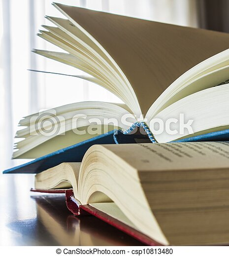 books over wood table with window light background - csp10813480