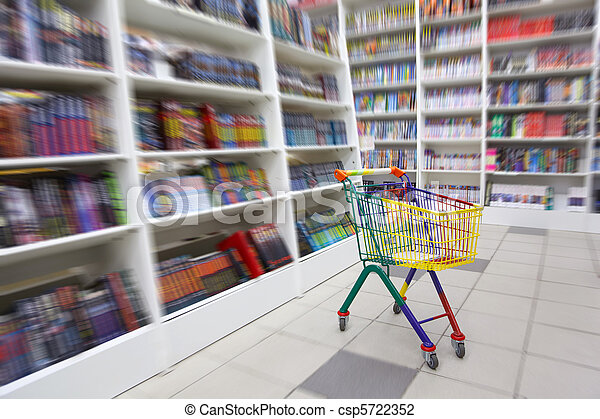 Bookshop interior. A in front of racks with books there is bright cart for purchases. - csp5722352