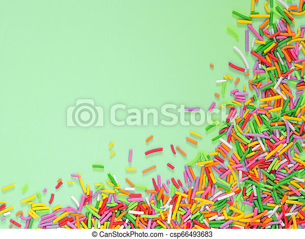 Border frame of colorful sprinkles on green background - csp66493683