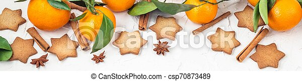 Border of Christmas star cookies with spices and mandarin on white background with copyspace. - csp70873489