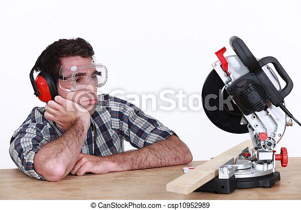 Bored man looking at circular saw - csp10952989