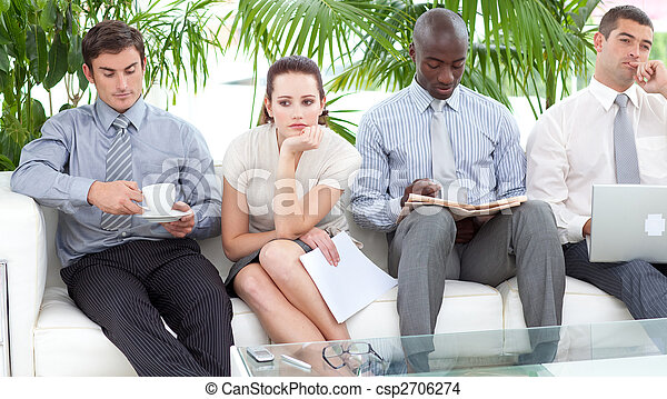 Bored multi-ethnic business people sitting on a sofa waiting for an interview - csp2706274
