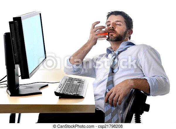 Hombre de negocios alcohólico bebiendo whisky sentado borracho en la oficina con ordenador - csp21798208
