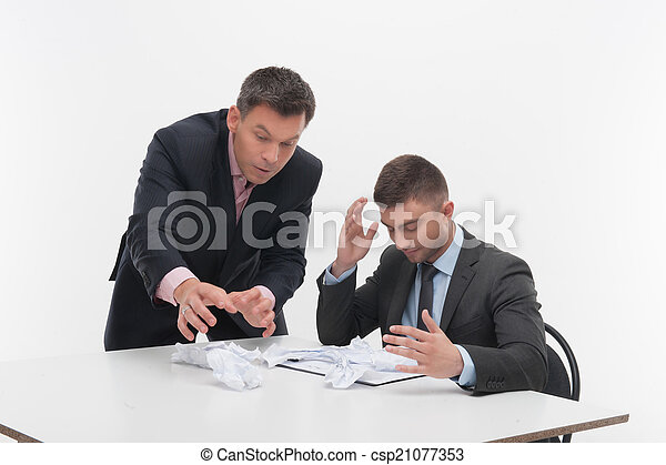 Boss angry with young employee sitting at desk - csp21077353