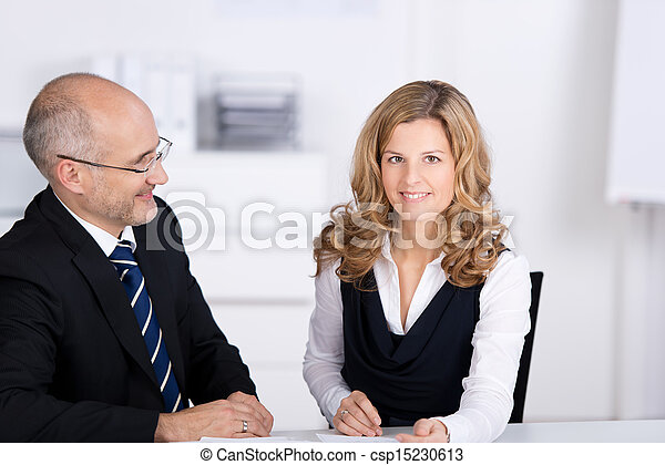 Boss sitting with an employee in the office - csp15230613