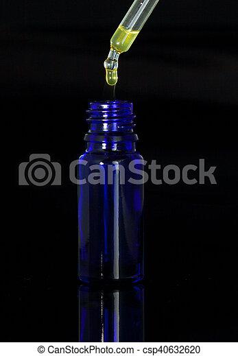 Botella de gota con gaitas en fondo negro - csp40632620