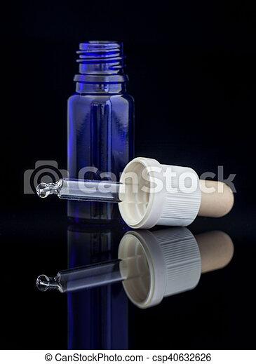 Botella de gota con gaitas en fondo negro - csp40632626
