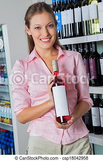 Una mujer con una botella de alcohol en el supermercado - csp18042958