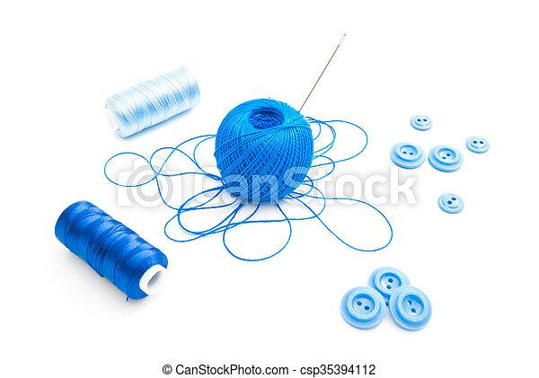 Un carrete de hilo, aguja y botones azules - csp35394112