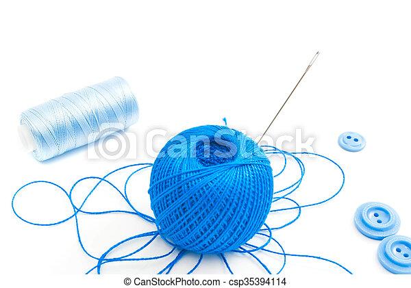 Un carrete de hilo, aguja y botones - csp35394114