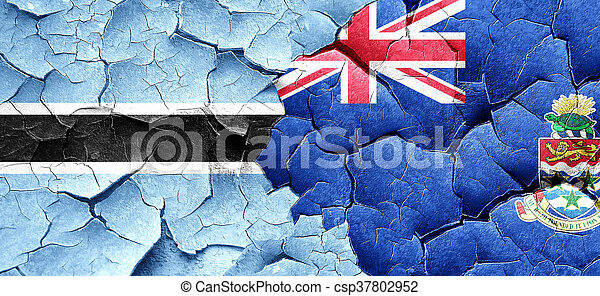 Botswana flag with Cayman islands flag on a grunge cracked wall - csp37802952