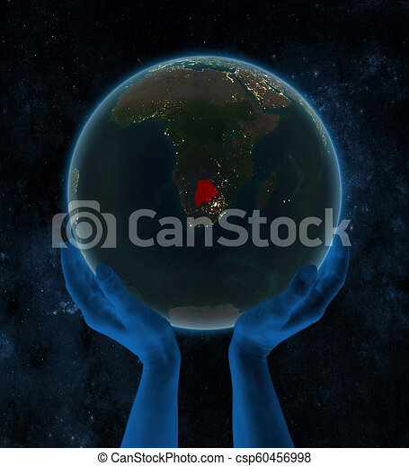 Botswana on night Earth in hands in space - csp60456998