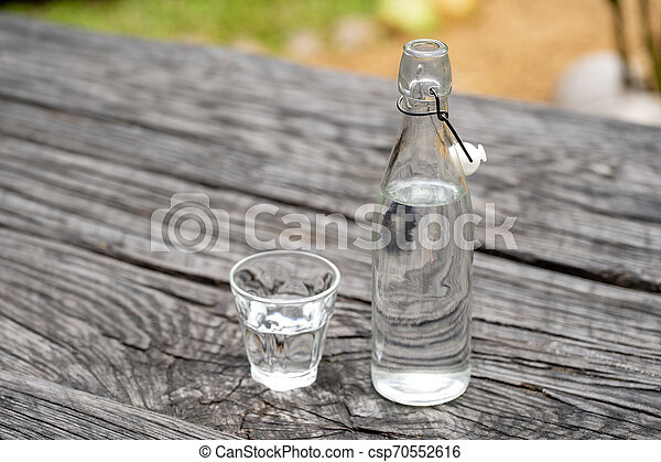 Bottle and glass with water on the wooden table - csp70552616