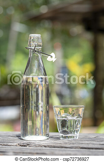 Bottle and glass with water on the wooden table - csp72736927