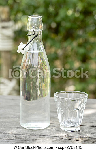 Bottle and glass with water on the wooden table - csp72763145