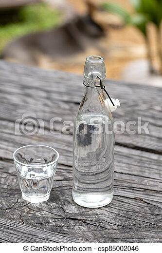 Bottle and glass with water on the wooden table - csp85002046