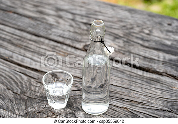 Bottle and glass with water on the wooden table - csp85559042