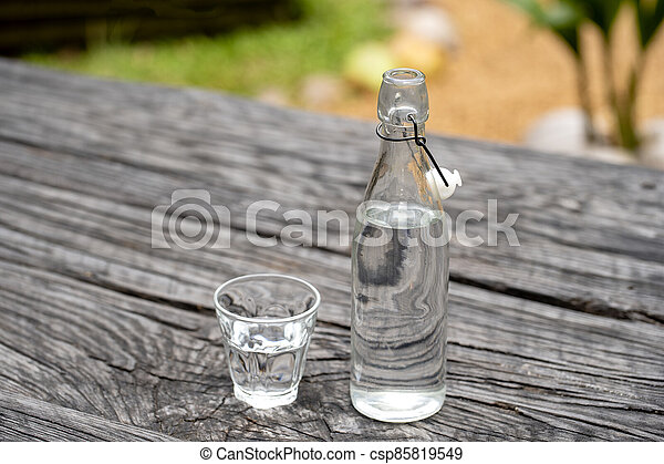 Bottle and glass with water on the wooden table - csp85819549