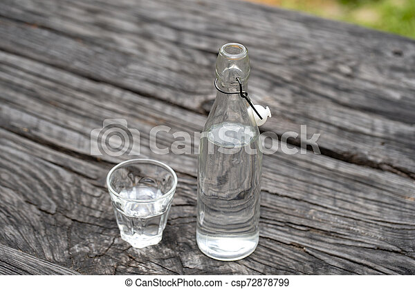 Bottle and glass with water on the wooden table - csp72878799