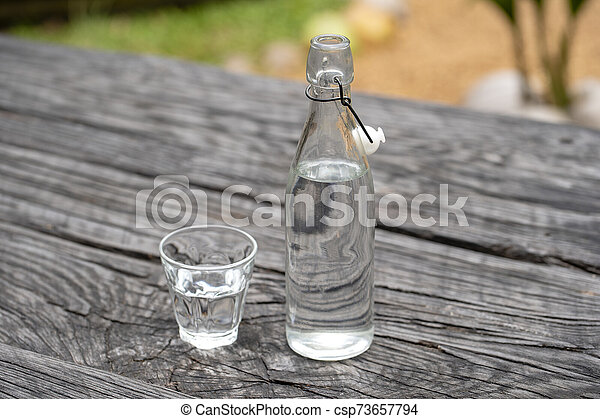 Bottle and glass with water on the wooden table - csp73657794