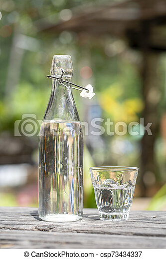 Bottle and glass with water on the wooden table - csp73434337