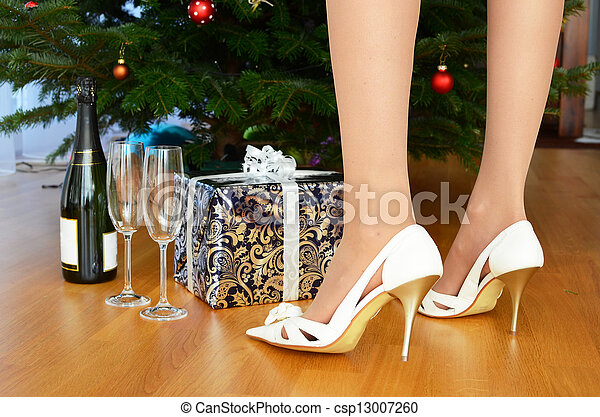 Bottle of champagne and a gift under the Christmas tree  - csp13007260