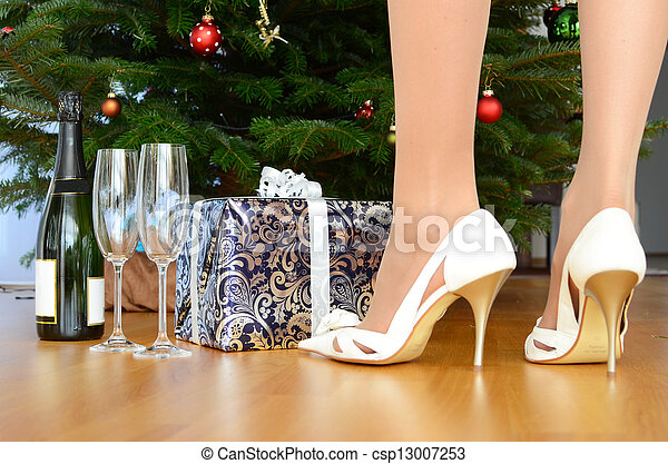 Bottle of champagne and a gift under the Christmas tree - csp13007253