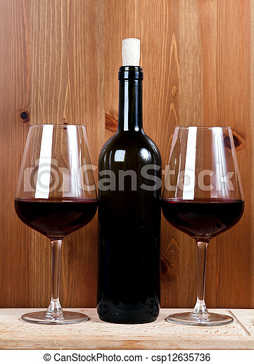 bottle of wine and two wineglasses with red wine - csp12635736