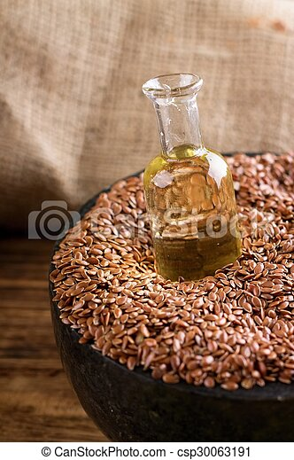 Bottle with flax oil in seeds - csp30063191