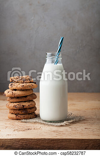 Bottle with milk and chocolate chip cookies on dark background with copy space - csp58232787