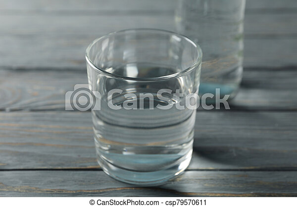 Bottle with water and glass on wooden table, close up - csp79570611