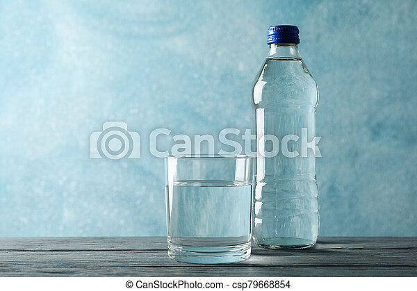 Bottle with water and glass on wooden table, space for text - csp79668854