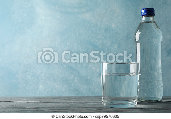 Bottle with water and glass on wooden table, space for text - csp79570605
