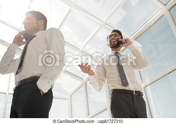 bottom view.business people talking on their mobile phone in the office. - csp61727310