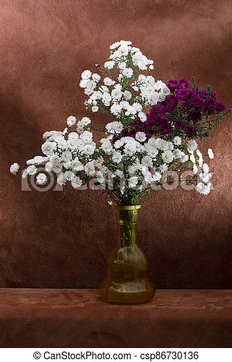 Bouquet of autumn asters in a glass vase on a brown background - csp86730136