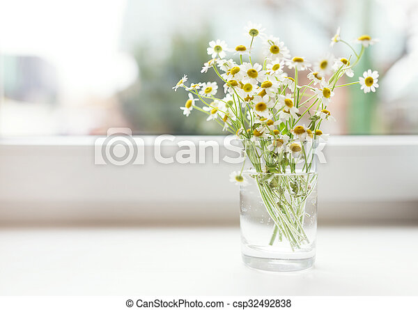 Bouquet of chamomiles flowers on the window sill - csp32492838