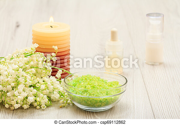 Bouquet of lilies of the valley, glass bowl with sea salt, burning candle, bottles with cream for face skin and aromatic oil. - csp69112862