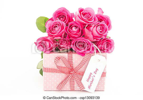 Bouquet of pink roses next to a pink gift with a happy mothers day card on white background close up - csp13093139