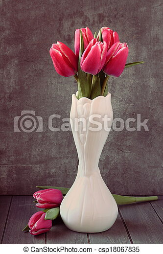 Bouquet of pink tulips in white vase on wooden background - csp18067835