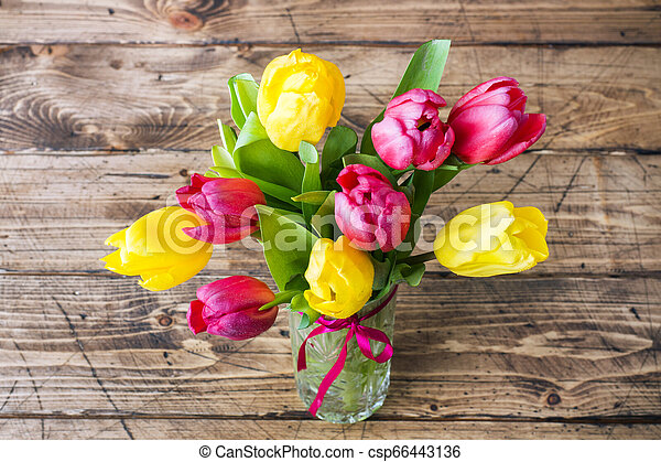 Bouquet of yellow and pink tulips on a wooden background. - csp66443136