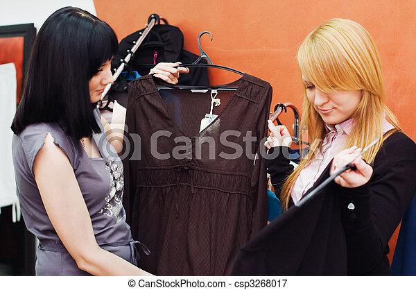 La chica elige ropa en una boutique - csp3268017