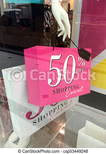 Boutique mannequin holding sale sign on shopping bag - csp53449248